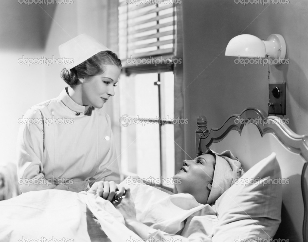 Nurse comforts a patient in a hospital bed, talking to each other