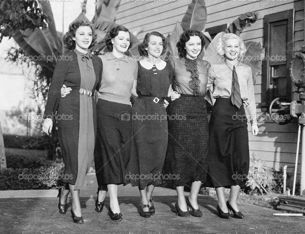 Five women posing in a back yard