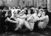 Skupina mladých žen sedí na podlaze obývacího pokoje mluví