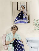Photo Woman sitting under the portrait of Betsy Ross sewing the American flag