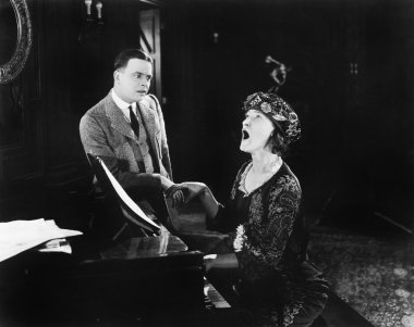 Man looking in horror at a singing woman