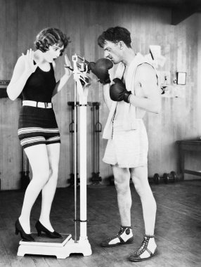 Young woman shocked at her weight with a man in boxing gloves