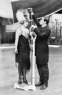 Man taking a measurement of a woman with an oversized hat