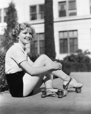 Woman in roller skates sitting on a sidewalk