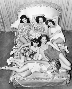 Six smiling young women lying on a bed