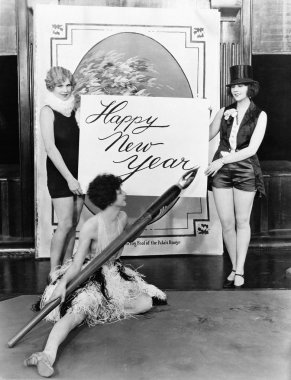 Women writing Happy New Year with huge pen
