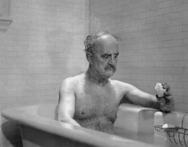 Man in bathtub glaring at soap