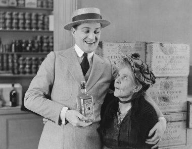 Senior woman looking at man holding gin bottle