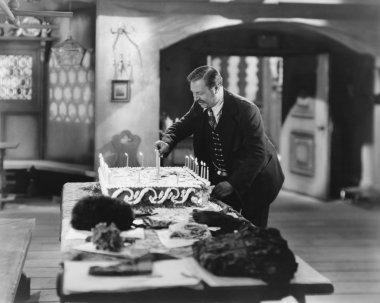Man lighting candles on cake