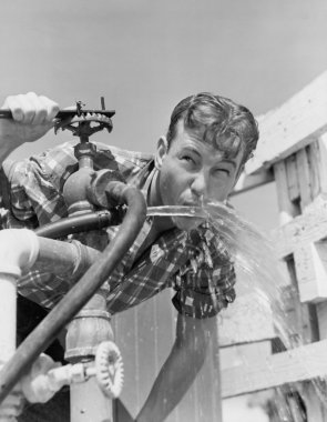 Young man drinking water from hose