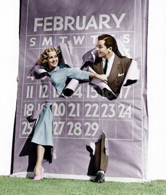 Couple bursting through leap year calendar