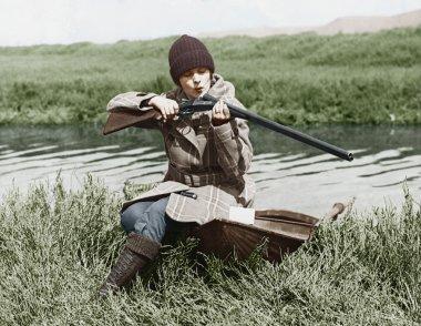 Female hunter with gun near river
