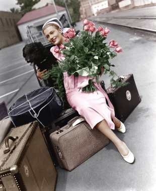 Woman with luggage flowers and dog