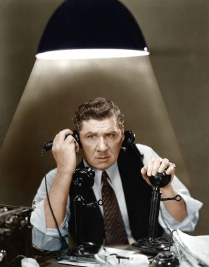 Man using two telephones