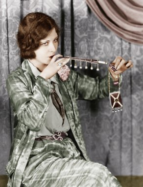 Young woman smoking a cigarette with a cigarette extension