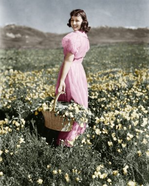 Rear view of a girl standing in a meadow holding a flower basket and smiling