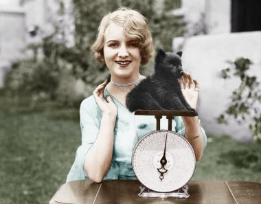 Portrait of a young woman weighing her puppy on a weighing scale