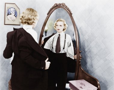 Young woman in men's clothing getting undressed in front of a mirror