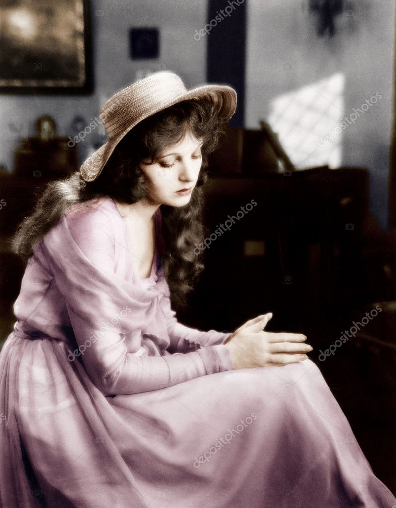 Young woman in a hat sitting and looking sad