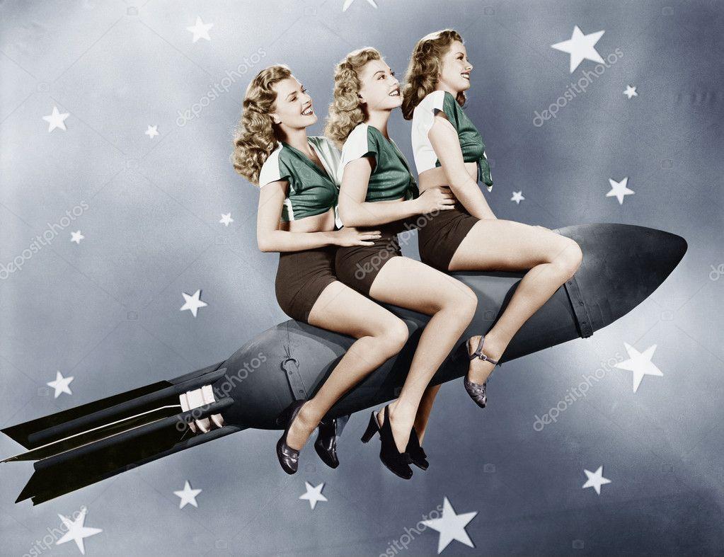 Three women sitting on a rocket