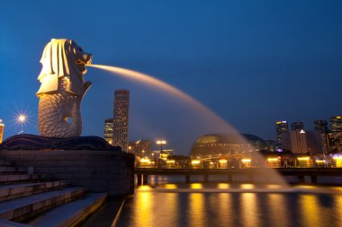 Merlion fountain spouts water of the Singapore skyline in night.