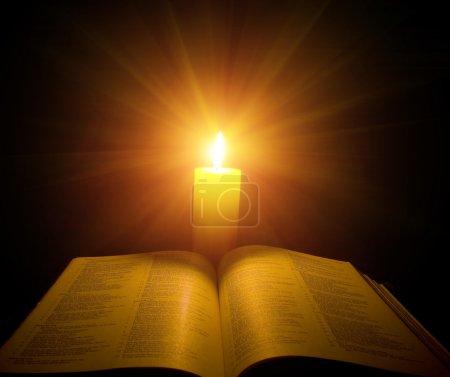 Photo pour Une bible ouverte sur une table à côté d'une bougie - image libre de droit