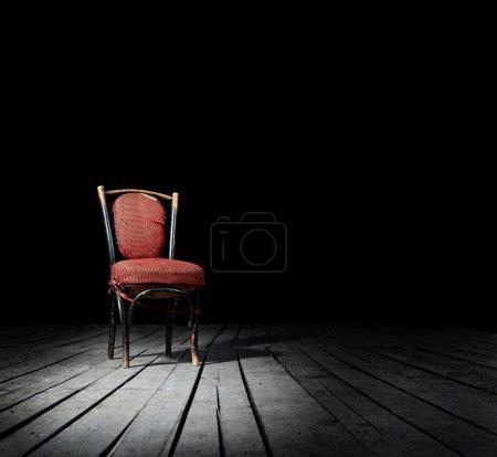 Photo pour Vieille chaise rouge façonné sur un plancher en bois - image libre de droit