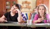 Unavený chlapec spí během lekce ve škole