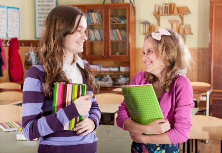 Two female classmates smiling in calssroom