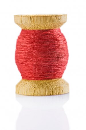 Small sewing spool with red thread