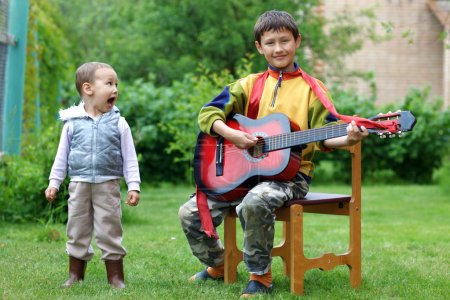 Two funny boys music student singing and playing the guitar outd