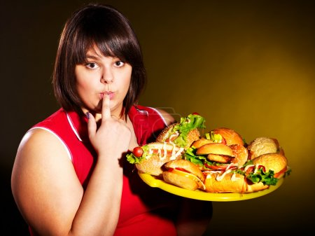 Photo for Overweight woman eating hamburger. - Royalty Free Image
