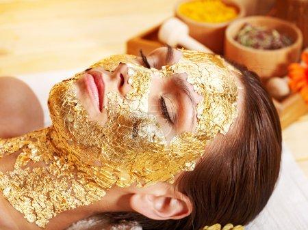 Foto de Mujer consiguiendo oro máscara facial . - Imagen libre de derechos