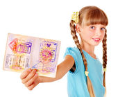 Child holding passport. Foreign vacation.