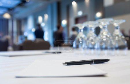 Photo pour Table de conférence avec verres et papier plume avec en arrière-plan - image libre de droit