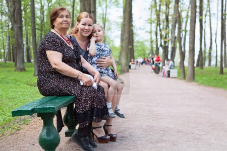 Three women different ages are sitting on bench in park