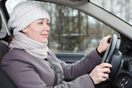 Photo pour Femme au volant d'une voiture vue intérieure des vêtements d'hiver - image libre de droit