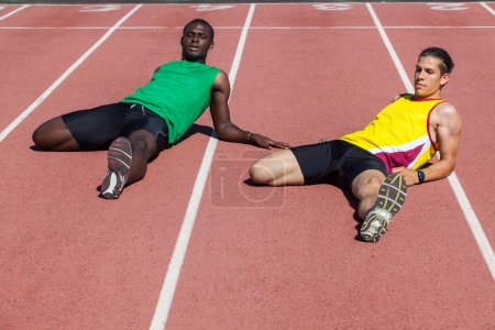 Photo for Two Track and Field Athletes Stretching - Royalty Free Image