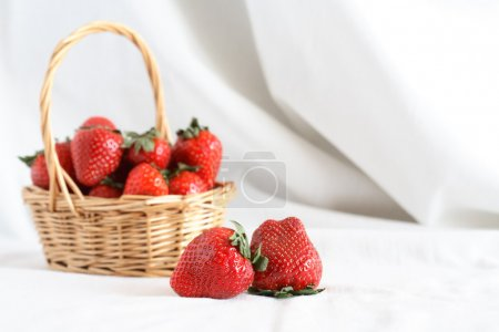 Photo for Nice wicker basket full of freshness red strawberry on white cloth background - Royalty Free Image