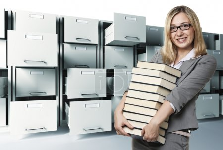 Photo for Smiling woman with books and file cabinet background - Royalty Free Image