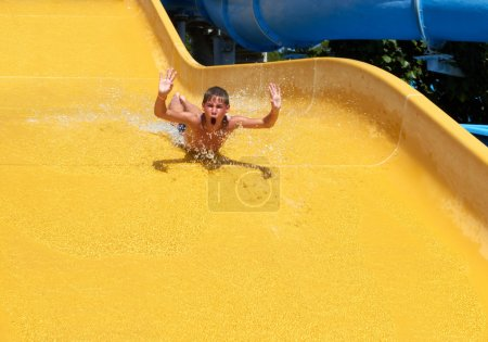 Photo pour Adolescent garçon roulant avec jaune toboggan à un parc aquatique - image libre de droit