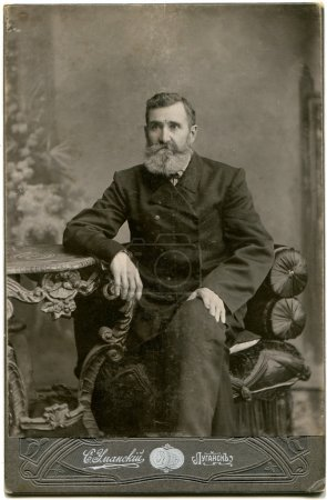 Photo for RUSSIA - CIRCA the end of 19 - early 20 century: An antique photo shows man in a business suit with a mustache and beard, sitting in a chair at the table, Lugansk, Russian Empire, now Ukraine Russian text: Umanskiy (photographer), Lugansk - Royalty Free Image