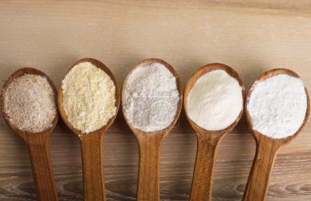Various types of flour in five wooden spoons...