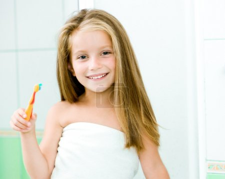 Photo for Reflection in the mirror of a little girl with toothbrush - Royalty Free Image