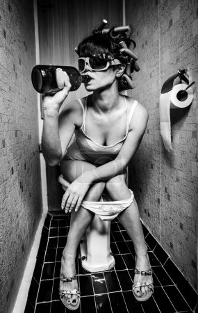 Photo for Girl sits in a toilet with an alcohol bottle - Royalty Free Image