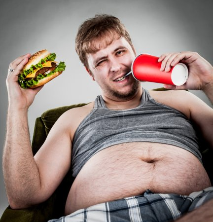 Photo for Fat man eating hamburger seated on armchair - Royalty Free Image