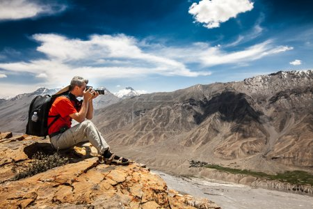 Photo for Photographer on the high mountain does its job. - Royalty Free Image