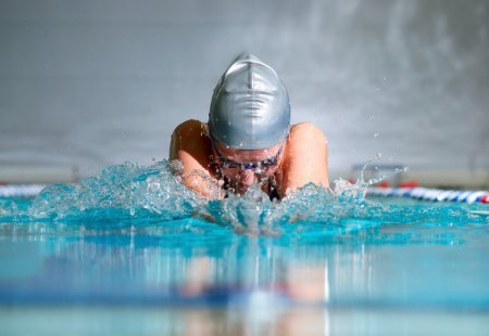 Photo for Woman swims using the breaststroke in indoor pool - Royalty Free Image