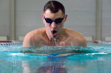 Man swims using the breaststroke in indoor pool