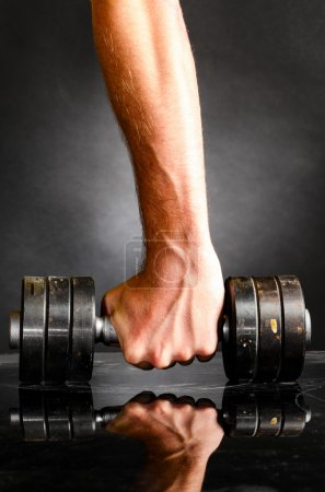 Male hand is holding metal barbell